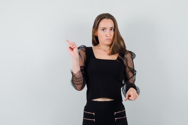 Jonge vrouw die tegengestelde richtingen met wijsvingers in zwarte blouse en zwarte broek richt en ernstig kijkt. vooraanzicht.