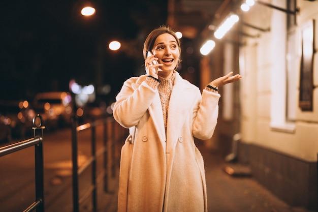 Jonge vrouw die telefoon buiten de nachtstraat met behulp van