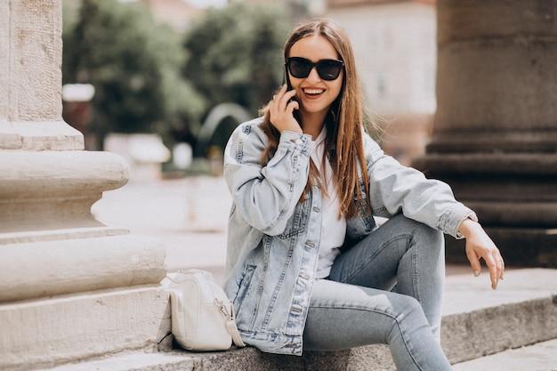 Jonge vrouw die telefoon buiten de stad met behulp van