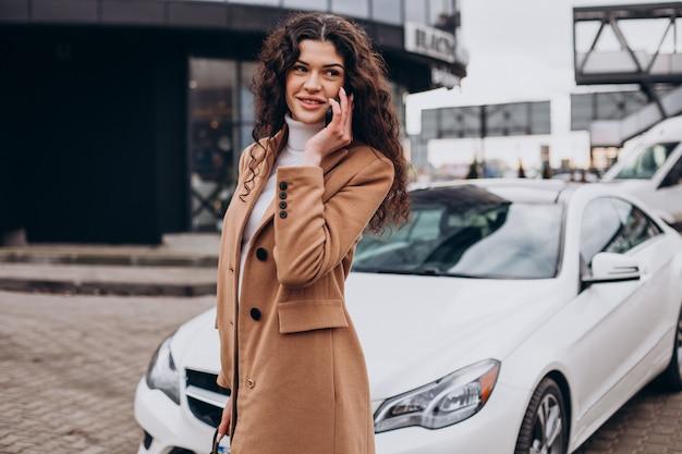 Jonge vrouw die telefoon gebruikt en bij de auto staat