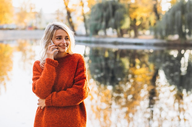 Jonge vrouw die telefoon in park door het meer met behulp van