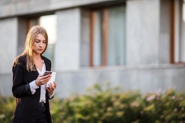 Jonge vrouw die telefoon medio schot bekijkt