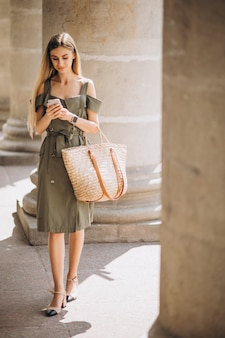 Jonge vrouw die telefoon met behulp van door het oude gebouw