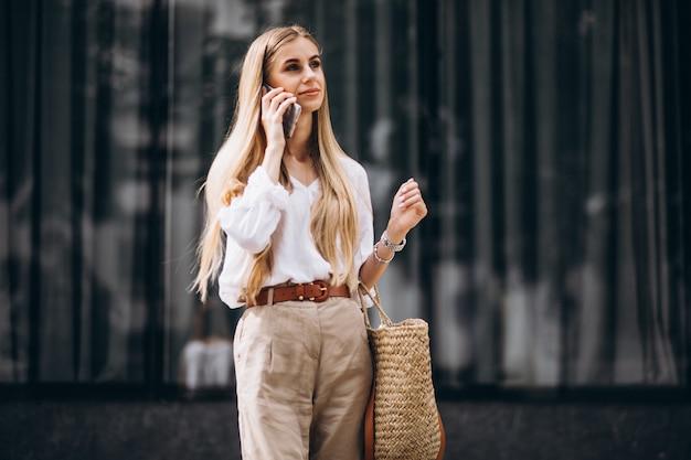 Jonge vrouw die telefoon uit in de stad met behulp van