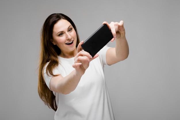 Jonge vrouw die telefoon voorstelt
