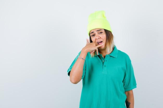 Jonge vrouw die telefoongebaar maakt in polot-shirt, muts en perplex kijkt. vooraanzicht.
