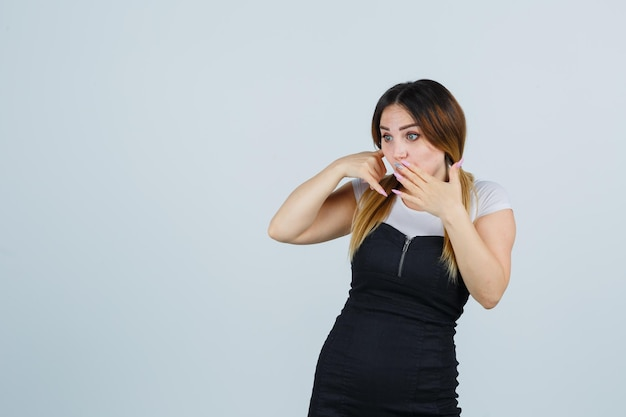 Jonge vrouw die telefoongebaar toont en verrast kijkt