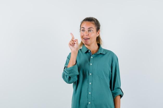 Jonge vrouw die terug in blauw overhemd wijst en nieuwsgierig kijkt