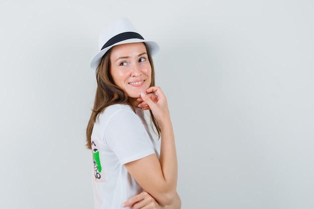 Jonge vrouw die terugkijkt terwijl zij in wit t-shirt, hoed denkt en optimistisch kijkt. .