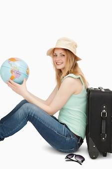 Jonge vrouw die terwijl het houden van een wereldbol glimlacht
