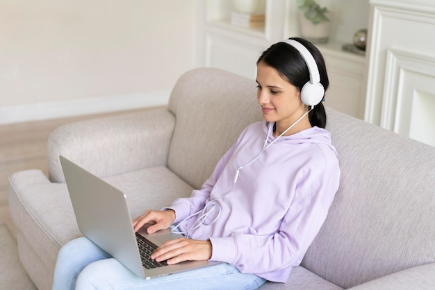 Jonge vrouw die thuis aan haar laptop werkt