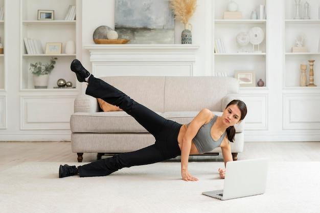 Jonge vrouw die thuis aan het trainen is Gratis Foto