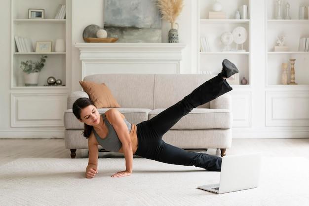 Jonge vrouw die thuis aan het trainen is