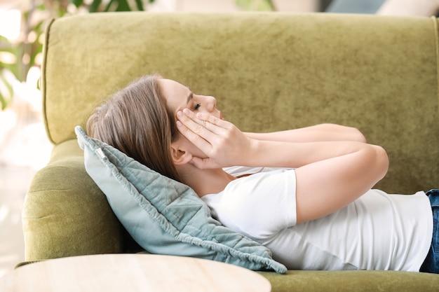 Jonge vrouw die thuis aan hoofdpijn lijdt