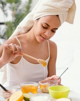 Jonge vrouw die thuis een natuurlijk gezichtsmasker maakt