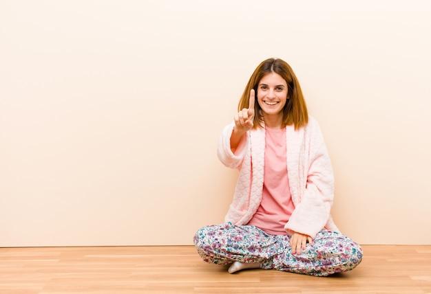 Jonge vrouw die thuis en pyjama's dragen die thuis glimlachen glimlachen kijken, nummer één tonen of eerst met vooruit hand, die aftellen