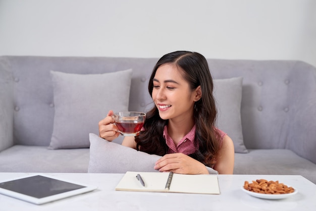 Jonge vrouw die thuis in de buurt van de bank zit en koffie drinkt