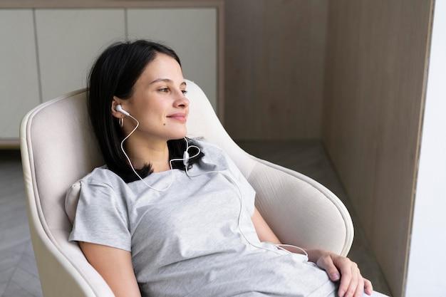 Jonge vrouw die thuis naar muziek luistert