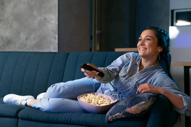 Jonge vrouw die thuis naar streamingdienst kijkt