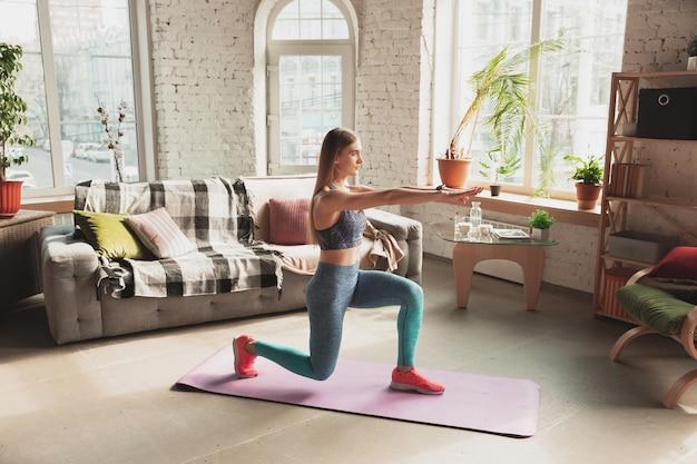 Jonge vrouw die thuis online cursussen geeft over fitness, aerobe, sportieve levensstijl