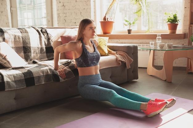 Jonge vrouw die thuis online cursussen van aëroob fitness onderwijst