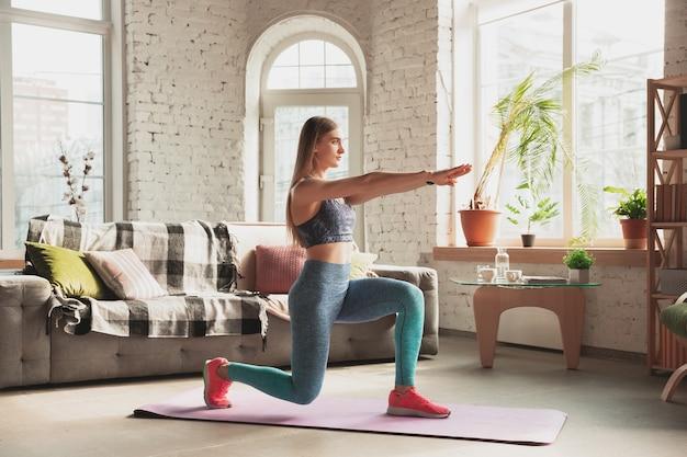 Jonge vrouw die thuis online fitnesscursussen geeft, aerobics.