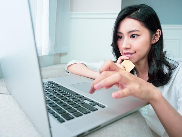 Jonge vrouw die thuis online winkelt met creditcard en laptop