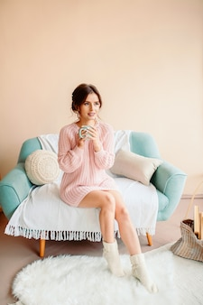 Jonge vrouw die thuis op een moderne stoel voor het venster zit, ontspannend in haar woonkamer, koffie of thee drinkt