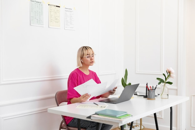 Jonge vrouw die thuis op haar laptop werkt