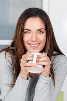 Jonge vrouw die thuis thee uit een kop nipt