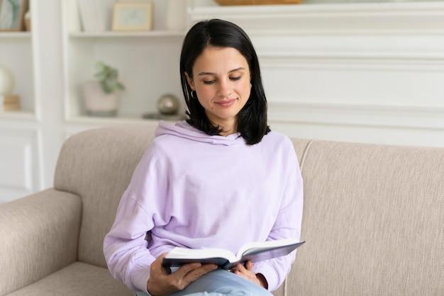 Jonge vrouw die thuis uit een boek leest