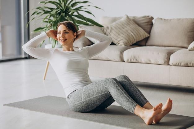 Jonge vrouw die thuis yoga beoefent op mat