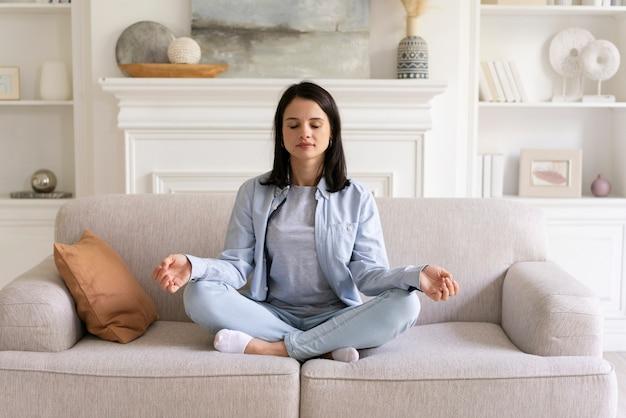 Jonge vrouw die thuis yoga doet