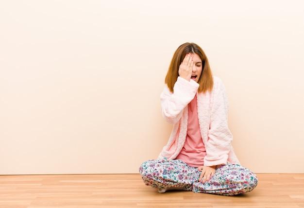 Jonge vrouw die thuis zit pyjama's kijken slaperig, verveeld en geeuwen, met hoofdpijn en één hand die de helft van het gezicht bedekken