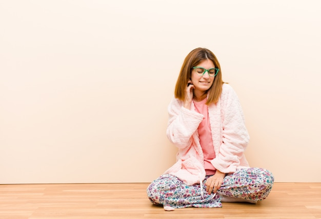 Jonge vrouw die thuis zit pyjama's voelt zich gestrest, gefrustreerd en moe, wrijft pijnlijke nek, met een bezorgde, onrustige blik