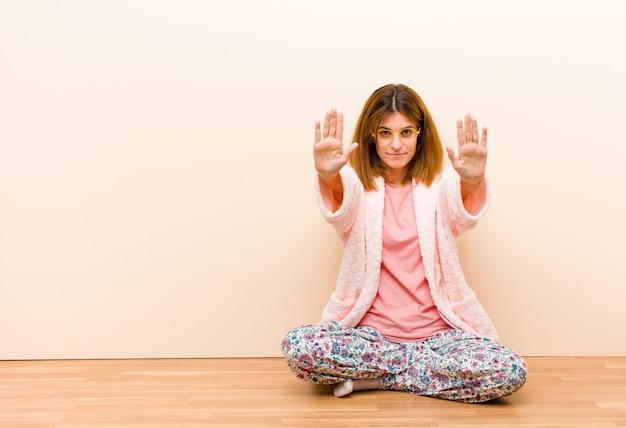 Jonge vrouw die thuis zittende pyjama's dragen die ernstig, ongelukkig, boos en ontevreden kijken die ingang verbieden of einde met beide open palmen zeggen