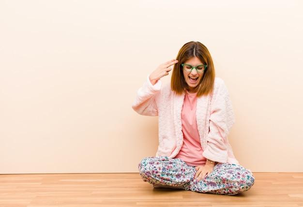Jonge vrouw die thuis zittende pyjama's dragen die ongelukkig en gestresst, zelfmoordgebaar maken die kanonteken met hand maken, die aan hoofd richten