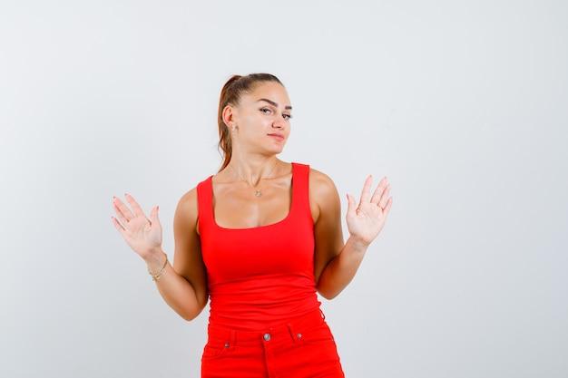 Jonge vrouw die tien vingers in rood mouwloos onderhemd, broek toont en wantrouwend, vooraanzicht kijkt.