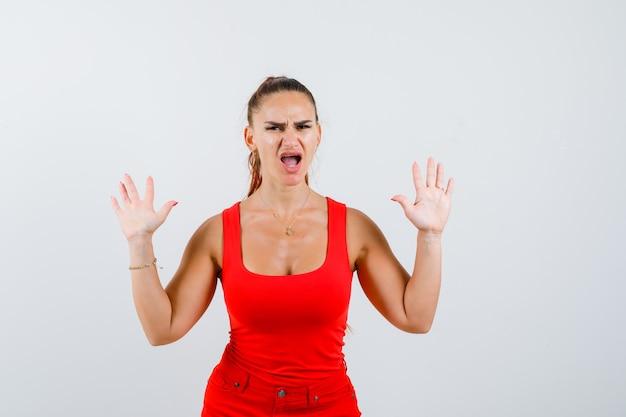 Jonge vrouw die tien vingers in rood mouwloos onderhemd, broek toont en wrokkig, vooraanzicht kijkt.