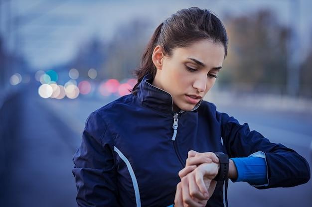 Jonge vrouw die tijd na het uitvoeren in straat controleert
