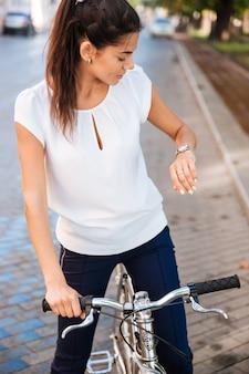 Jonge vrouw die tijd op haar polshorloge kijkt terwijl het zitten op de fiets