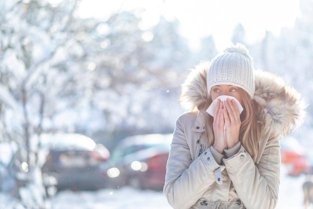 Jonge vrouw die tijdens de winter op straat hoest.