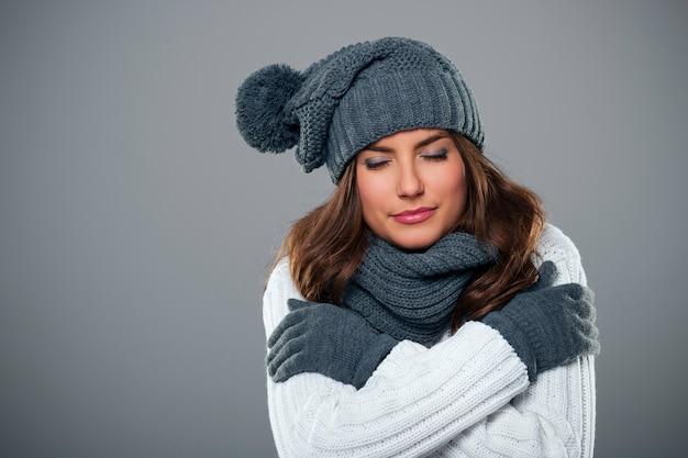 Jonge vrouw die tijdens het winterseizoen huivert