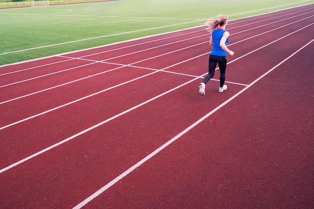 Jonge vrouw die tijdens zonnige avond op stadionspoor loopt. een blondine in een blauw t-shirt en zwarte legging rent door het stadion.