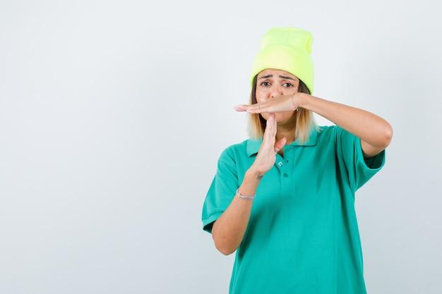 Jonge vrouw die tijdpauze gebaar toont in polo t-shirt, muts en boos kijkt, vooraanzicht.