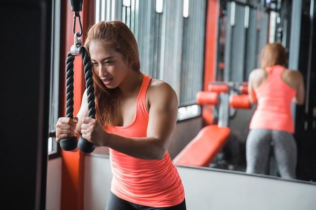 Jonge vrouw die tricepspushdown uitoefenen