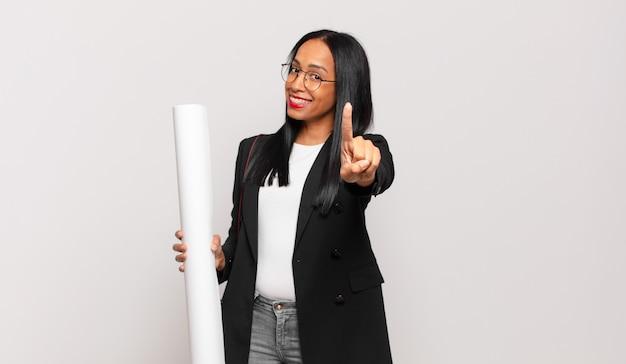 Jonge vrouw die trots en zelfverzekerd lacht en nummer één triomfantelijk poseert, voelt zich een leider