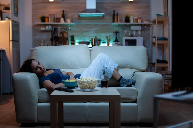 Jonge vrouw die tv kijkt en zich verveelt terwijl ze thuis op de bank in de woonkamer zit