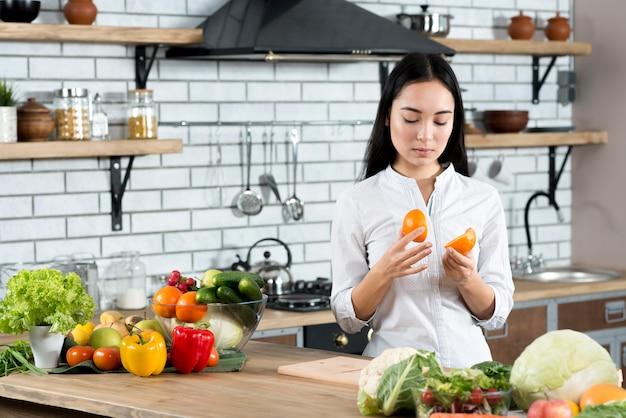 Jonge vrouw die twee halve sinaasappelen in keuken thuis bekijkt