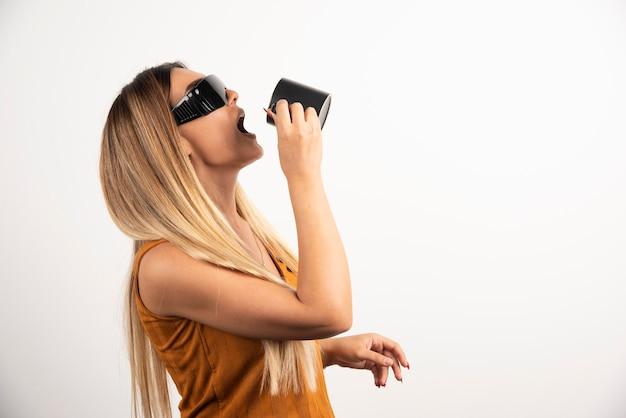 Jonge vrouw die uit zwarte kop drinkt en een veiligheidsbril draagt.
